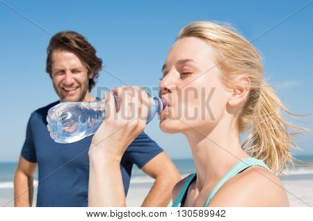 Young woman drinking water after workout. Handsome man looking at his woman at beach on a summer morning. Woman drinking water after run on beach with her boyfriend.