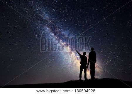 Silhouette of a father and a son who pointing finger in night starry sky on the background of Milky Way. Family. Colorful night landscape. Beautiful Universe. Space. Travel background with sky full of stars