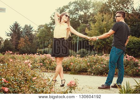 Love romance relationship dating concept. Cheerful girl holding hands in park. Young girl and boy taking walk.