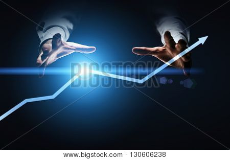 Financial growth concept with businessman hands willing to grab illuminated arrow pointed upwards