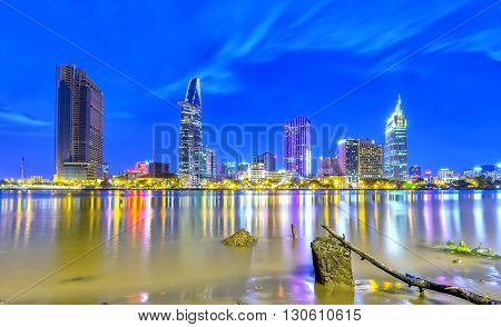 Ho Chi Minh City, Vietnam - May 20th, 2016: Beauty architecture along river with shining skyscrapers shimmering electric light illuminates smooth down river, path ahead spike navigate through urban tree expression desire to reach development in Ho Chi Min