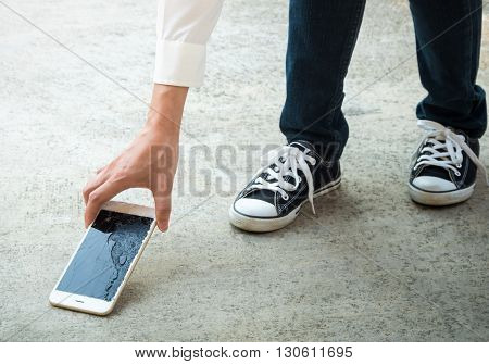 Person Picking Broken Smart Phone (Cracked Screen) of the Ground