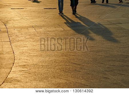 blurred background summer park with people and shadows. focus is on Pavement foreground. summer sunset