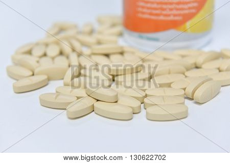 Many pills on the white table with a bottle of pills