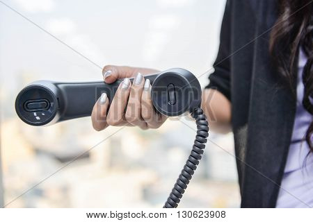 Business woman is holding the IP Phone handset