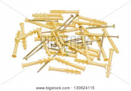 Pile of yellow plastic wall plugs and zinc plated chipboard screws with countersunk heads on a light background