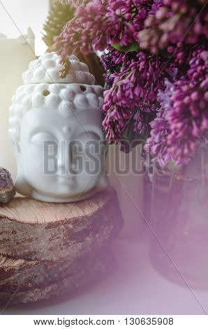 Spiritual zen meditation face of Buddha with beautiful violet branch lilac flowers. Home decor still life concept. Sweet pastel soft background.