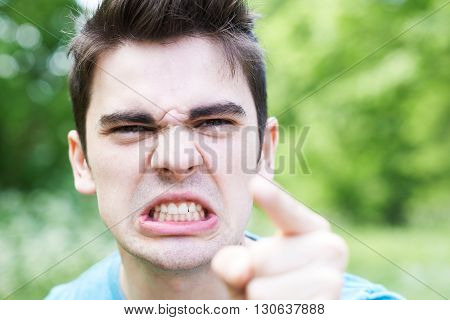 Outdoor Head And Shoulders Portrait Of Angry Young Man