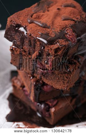 Closeup of homemade chocolate sweet brownies cakes with cherry and chocolate sauce or syrup on a dark background