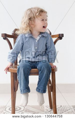 little curly-haired girl sitting on a chair and laughs, looking in the direction, wears  blue long sleeve shirt and jeans