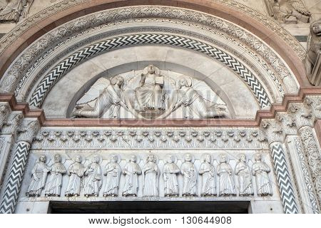 LUCCA, ITALY - JUNE 06, 2015: portal of the Cathedral of St Martin in Lucca. Lunette depicts the Redeemer in a mandorla held by two angels and Virgin Mary with Apostles, Lucca, Italy, on June 06, 2015