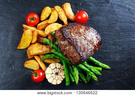 Beef steak Mignon cooked with Asparagus, potatoes, garlic and tomatoes. Served on blue stone board.