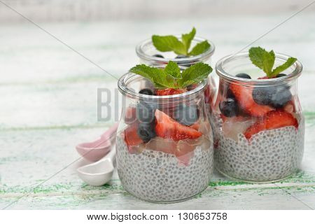 Chia pudding with strawberries and blueberries on a white background