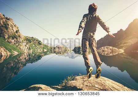 Man jumping Flying levitation with lake and mountains on background Lifestyle Travel happy emotions concept outdoor