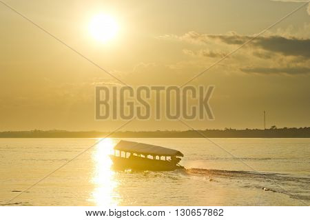 boat on river amazon at yellow sunset in Peru