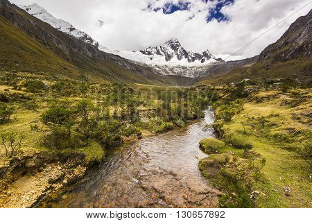 panorama of snow-covered Andes mountains and river in Peru and blue lake from path to punto union pass