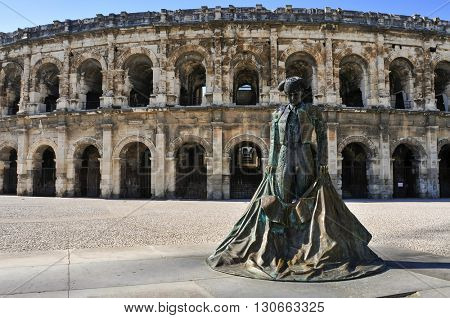 NIMES, FRANCE - MAY 12: Statue of bullfighter Christian Montcouquiol, Nimeno II, in front of the Arena of Nimes on May 12, 2015 in Nimes, France. This Roman amphitheater serves as bullring since 1863