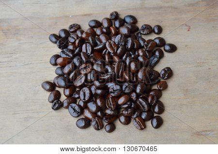 dark roast coffee seed on wooden board
