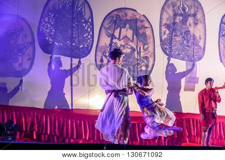 RATCHABURI THAILAND - APRIL 14 2015: The Cowskin shows a man holding a stencil pattern. Moving Cowskin the light to shadow play. The musical atmosphere and read a poem composed. In a traditional culture. There are performances every year Thailand in SONGK