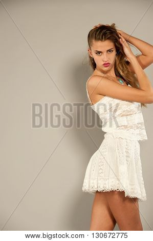 Hot brunette model with wavy hair wearing white skirt and top on a grey background in a studio setting. She looks passionately at the camera and is seen from knees up.