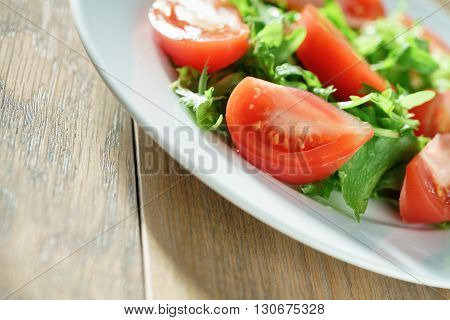 closeup photo of fresh summer salad with tomatoes, rucola and frillis leaves in plate on wood table, shallow focus