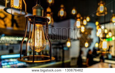 Edison bulb glowing in the dark blurred background