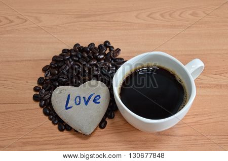 heart stone with black coffee cup and seed