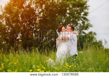 Expressive couple sincerely hugging themself on the sunset meadow.