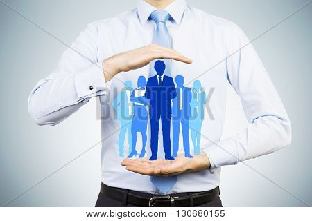 Human recources and employee care concept with man holding businesspeople silhouettes