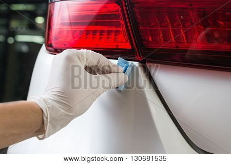 Car detailing series : Closeup of hand coating white car paint