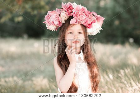 Cute baby girl 3-4 year old with peony wreath outdoors. Looking at camera. Childhood.