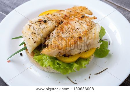 Sandwich with grilled fish, pepper and letucce on the plate