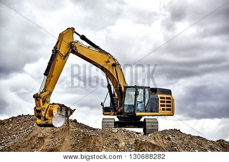 Construction industry heavy equipment excavator moving gravel at jobsite quarry with stormy skies poster