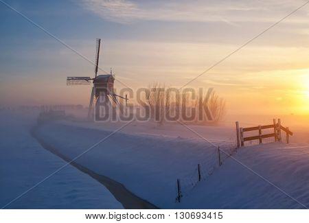 Wingerdse mill near Oud-Alblas in the Dutch region Alblasserwaard in a misty and wintry landscape