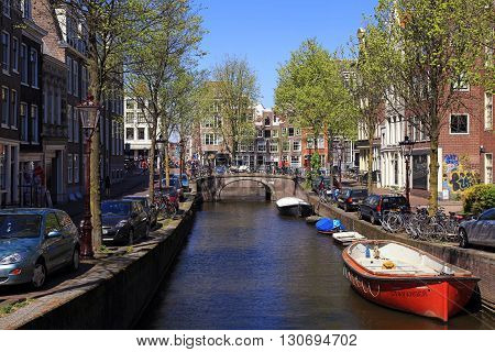 AMSTERDAM, NETHERLANDS - MAY 8, 2016: Beautiful city veiw with canal bridge boats and traditional houses typical picture of canals in Amsterdam, Netherlands.