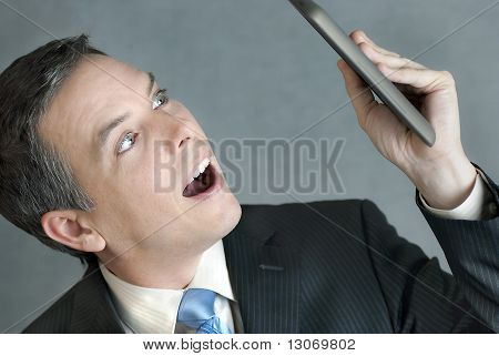 Businessman Looks At Tablet In Awe