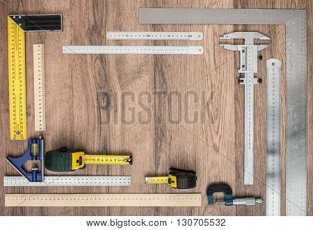 Measuring tools on wooden background. Wooden and metal rulers tape measures tape-lines micrometers set squares.