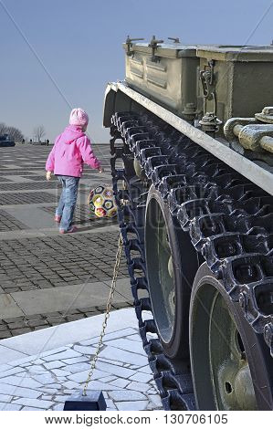 KYIV UKRAINE - MAY 09 2015: The seventieth anniversary of the terminal of the Second World War. Merry child in cheerful pink color anorak with ball plays near khaki heavy steel war tank under blue sky on square of museum SWW.