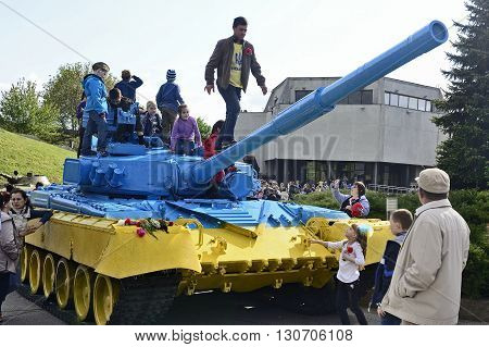 KYIV UKRAINE - MAY 2015: The seventieth anniversary of the terminal of the Second World War. Children on old USSR heavy tank painted in Ukrainian flag colors in the state museum of Second World War