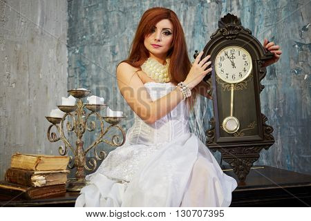 Red-haired woman in white dress sits on old grand piano lid holding pendulum clock.