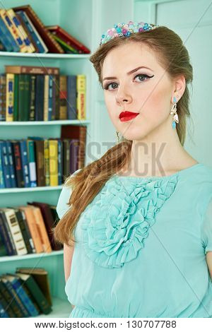 Young woman in green dress at library, half-length portrait.