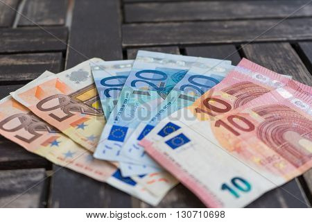 Pile of euro bank notes. Ten twenty and fifty euro bank notes on wooden background. Paper money on wooden background - Very soft focus.