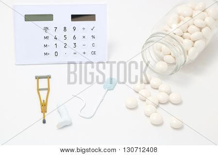 White pills spilling out of a  transparent medicine bottle and small items of illness or injury on white background.