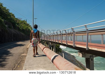 Rio de Janeiro, Brazil - April 22, 2016: A boy walks on the edge of Niemeyer avenue along with the newly built Tim Maia bicycle path.