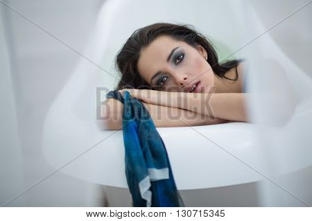 Lovely girl sits in a white bath and looks into the camera with parted lips. She leans on a bath with crossed hands. Her head leans on her hands. She holds a blue scarf in her left hand. There are light curtains on the sides. Horizontal.