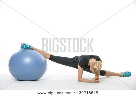 Beautiful gymnast girl in the sportswear with a blue fitball on the white background in the studio. She wears cyan-yellow sneakers, black pants and black t-shirt. She makes the splits: she leans on her elbows while her right leg is on the fitball and left