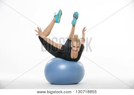 Gymnast girl in the sportswear lies on a blue fitball on the white background in the studio. She wears cyan-yellow sneakers, black pants and black t-shirt. She holds her stretched legs and arms in the air. She looks into the camera with a smile. Horizonta