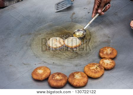 Local delicacies being cooked in a shop at Delhi market. Delhi is famous for spicy Indian foods and the cuisines are inevitably famous among both tourists and locals.