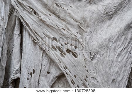 Old grey dirty torn rag hanging texture