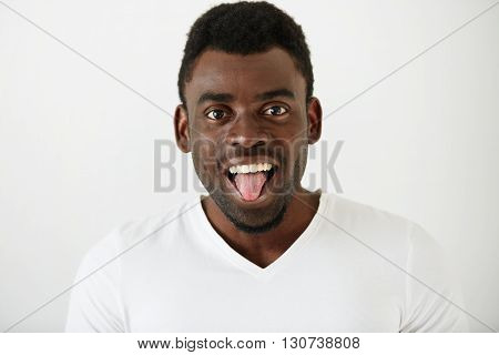 Close Up Portrait Of African American Student Boy Wearing White T-shirt Making Funny Face, Looking A